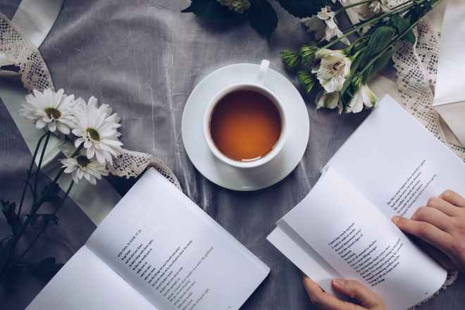 Two open faced books with coffee cup and flowers create peaceful aesthetic.
